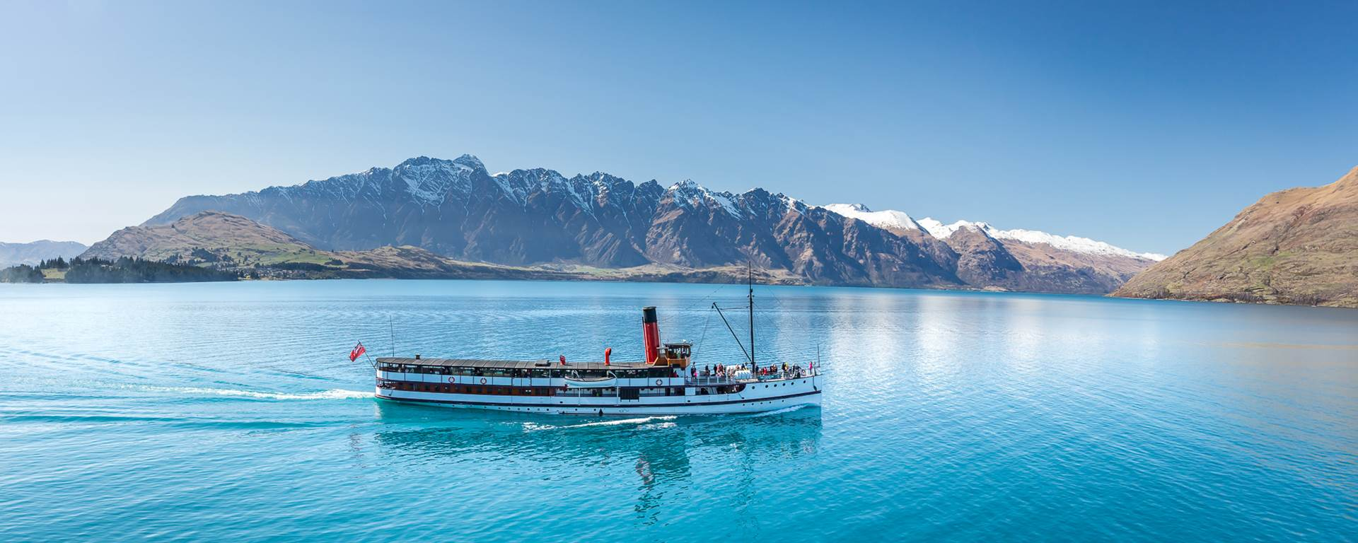 The TSS Earnslaw cruises across Lake Wakatipu with Remarkables in the background