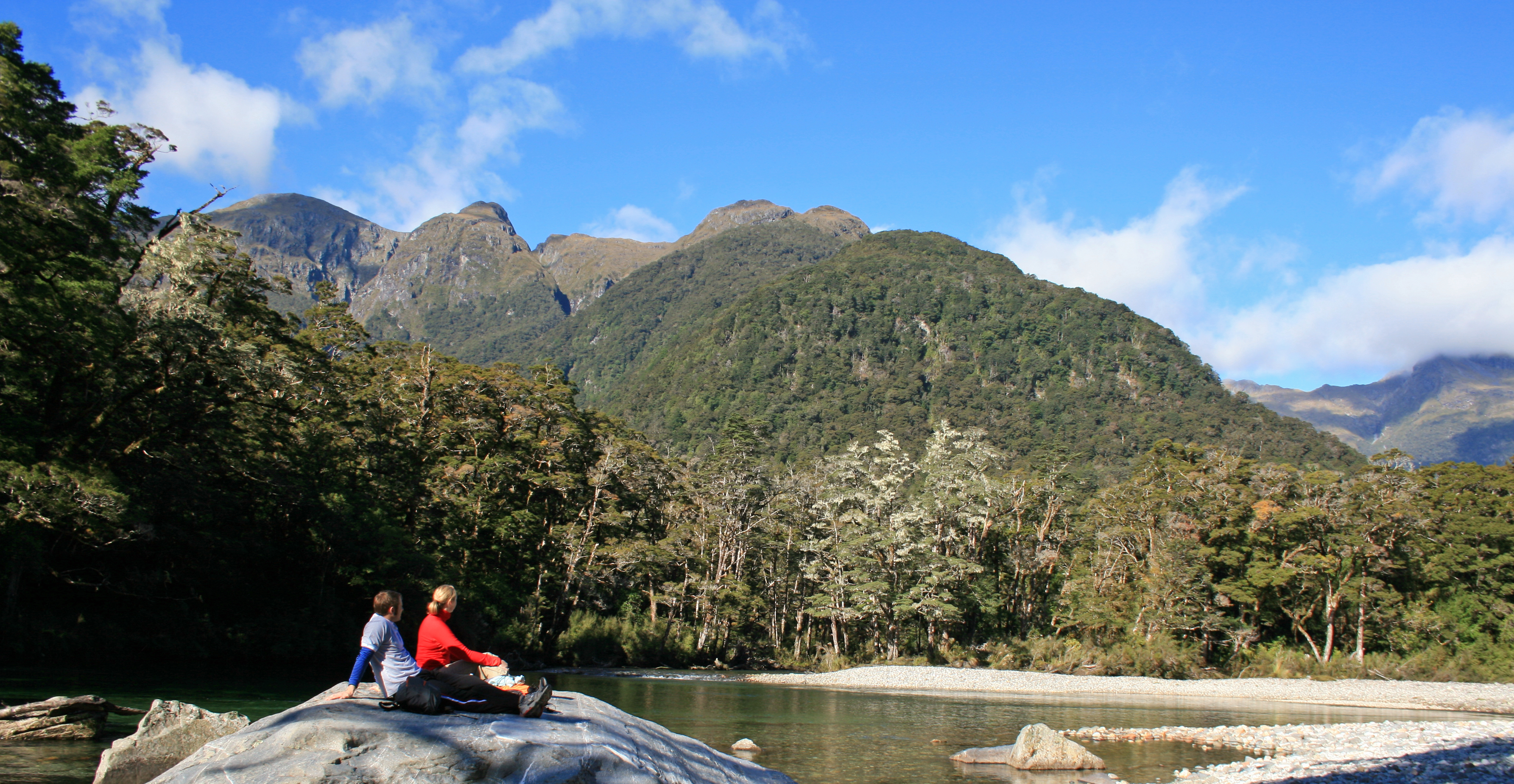 Walkers sit on a rock during the Milford Track Guided Day Walk