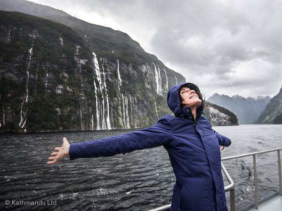 Woman enjoying the waterfalls in Fiordland National Park