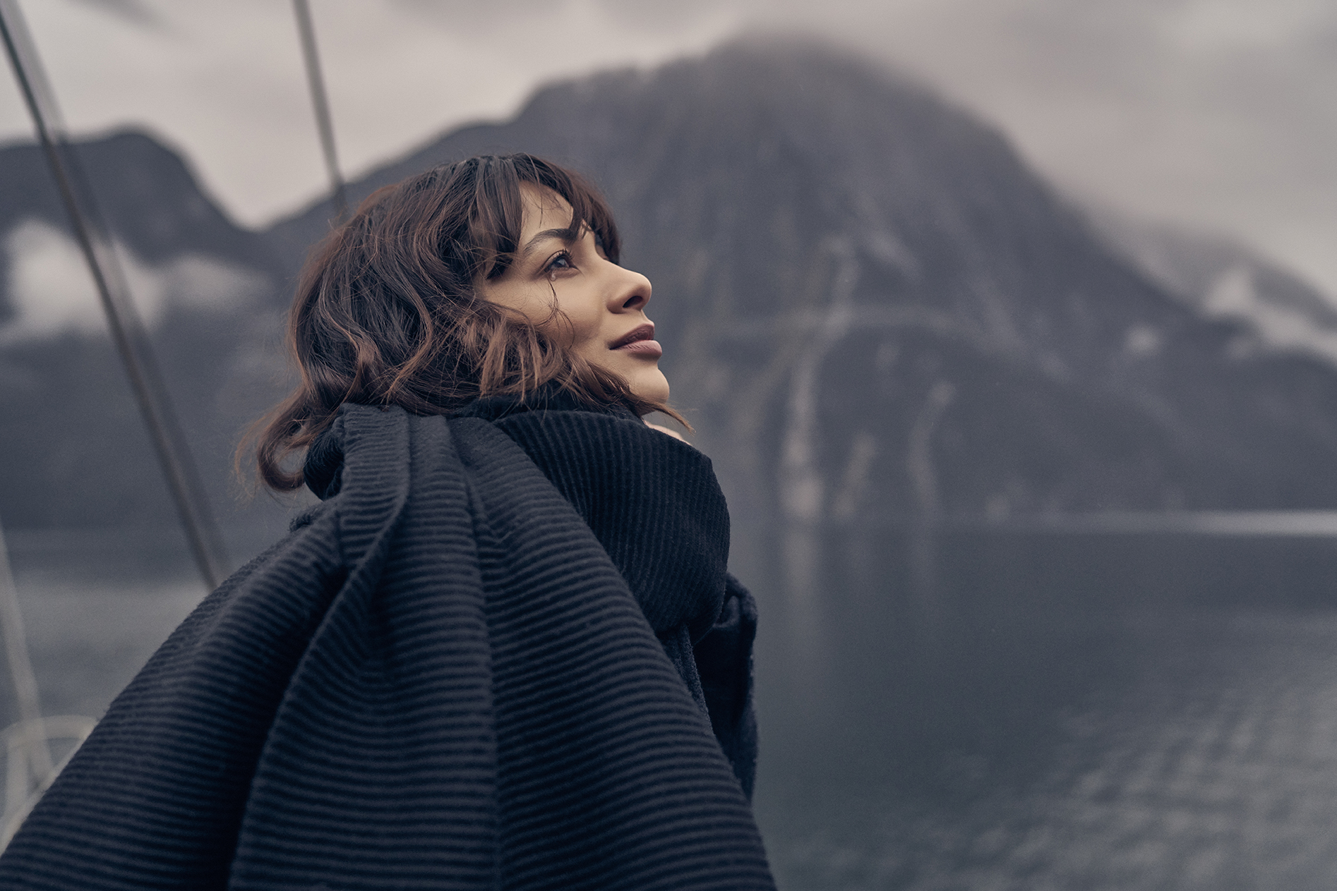 Woman looks at mountains in Milford Sound