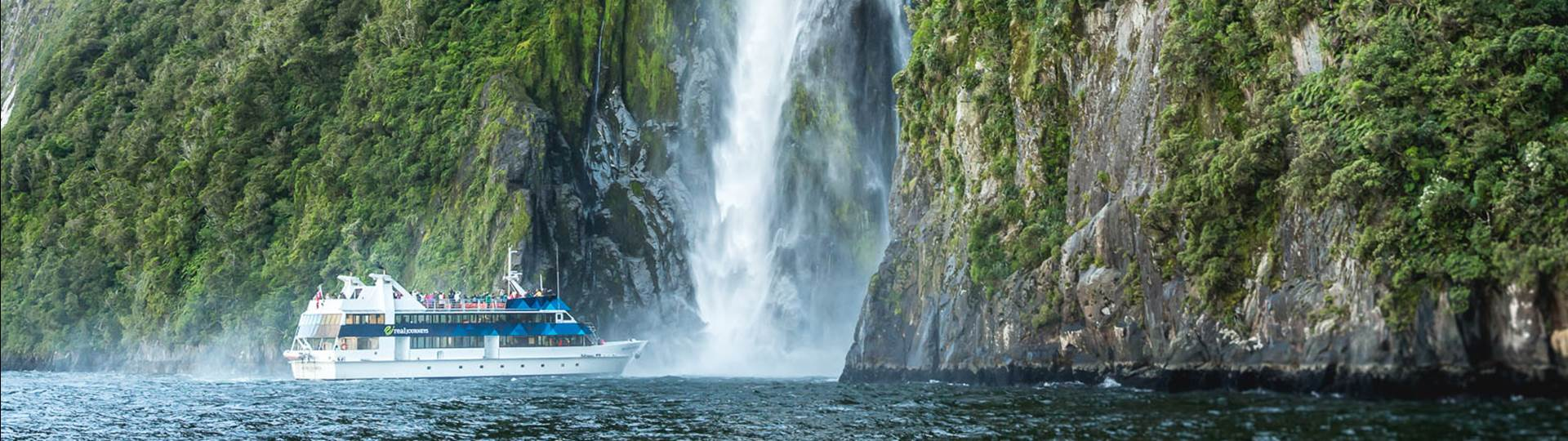 Boat under a waterfall in Milford Sound